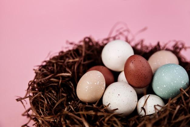 Uova di pasqua pastelli nel nido su superficie rosa come decorazione domestica, concetto di festa di stagione