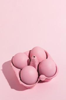 Uova di pasqua rosa in rack sul tavolo