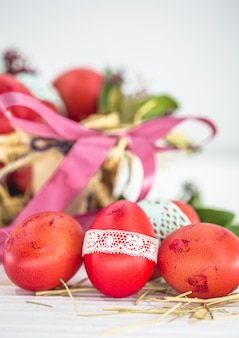 Uova di pasqua rosse legate primo piano nastro di pizzo, che giace in un cestino di pasqua con un fiocco, natura morta