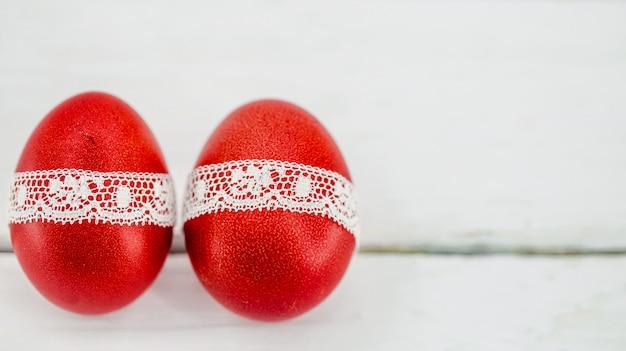 Uova di pasqua rosse su un bianco legate con un nastro di pizzo, primo piano, sdraiato su un legno bianco