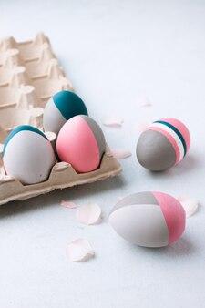 Uova di pasqua rustiche. natura morta di belle uova di pasqua dipinte sulla tavola bianca. concetto di individualità, essendo diverso, organico, tatuaggio sull'uovo.