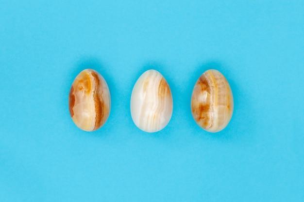 Uova di pasqua su carta blu uova decorative di pietra texture. concetto di celebrazione di primavera.