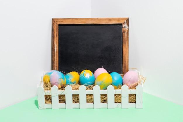 Uova di pasqua su fieno in scatola con la lavagna