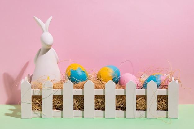 Uova di pasqua su fieno in scatola con statuetta di coniglio