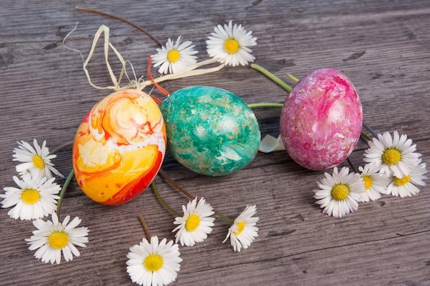Uova di pasqua su fondo di legno, con fiori per carta