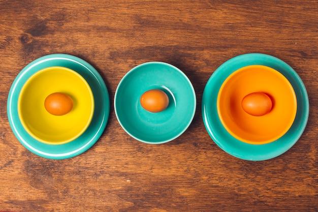 Uova di pasqua su piatti luminosi e ciotole