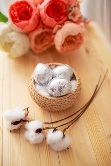 Uova di pasqua sulla tavola di legno bianca. fiori e caramelle intorno.