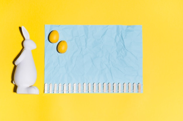 Uova di pasqua sullo strato di carta con coniglio sul tavolo