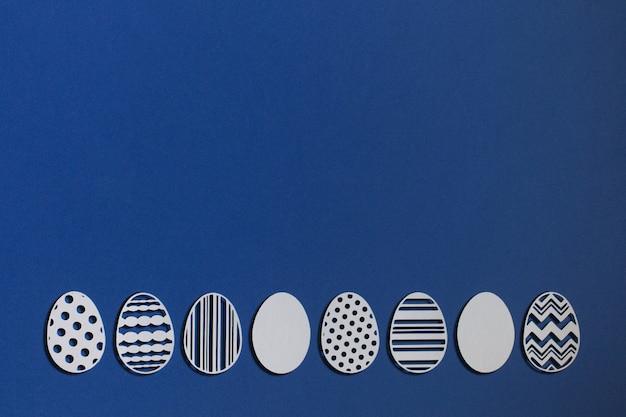 Uova di pasqua tagliate da carta su sfondo blu classico, colore 2020 classic blue pantone