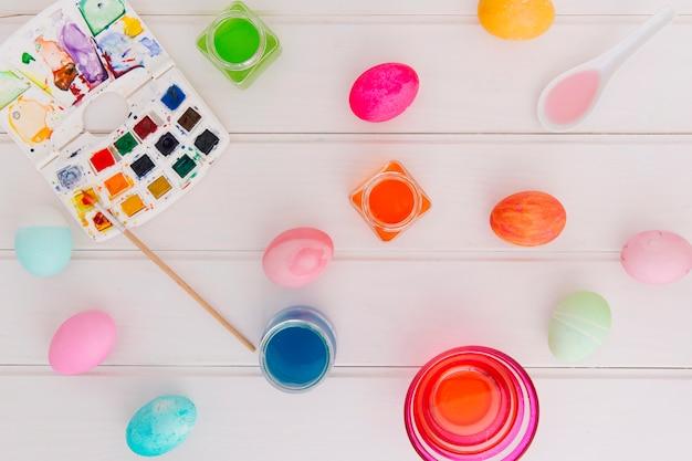 Uova di pasqua tra tazze con liquido di tintura vicino a cucchiai e pennello con set di colori