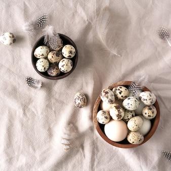 Uova di pasqua, uova di quaglia e piume bianche e marroni su fondo di tela naturale. sfondo di pasqua
