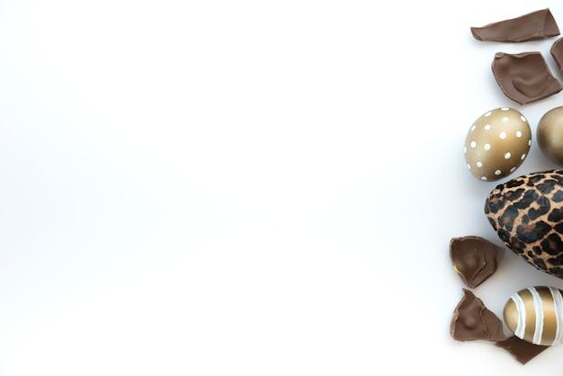 Uova di pasqua variopinte con l'uovo di cioccolato sulla tavola bianca