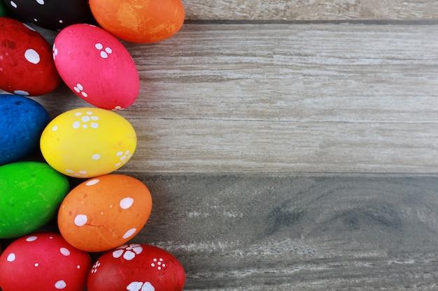 Uova di pasqua variopinte e decorate sulla tavola di legno d'annata