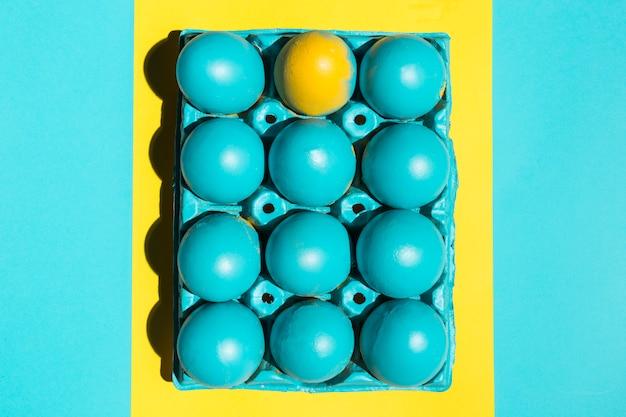 Uova di pasqua variopinte in scaffale nel telaio sul tavolo