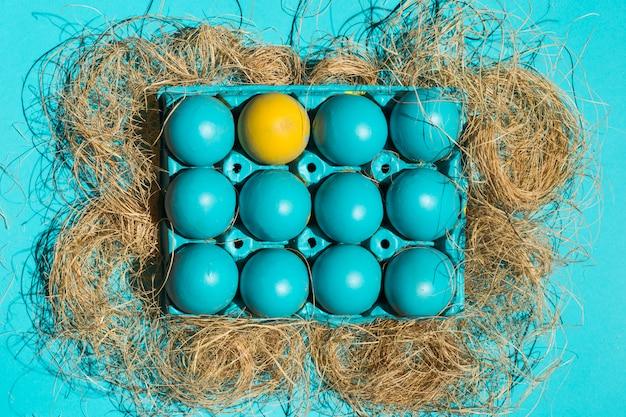 Uova di pasqua variopinte in scaffale su fieno sulla tavola