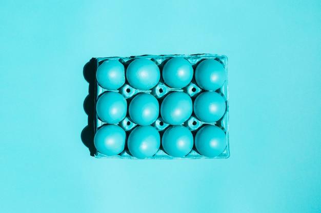 Uova di pasqua variopinte in scaffale sulla tavola blu