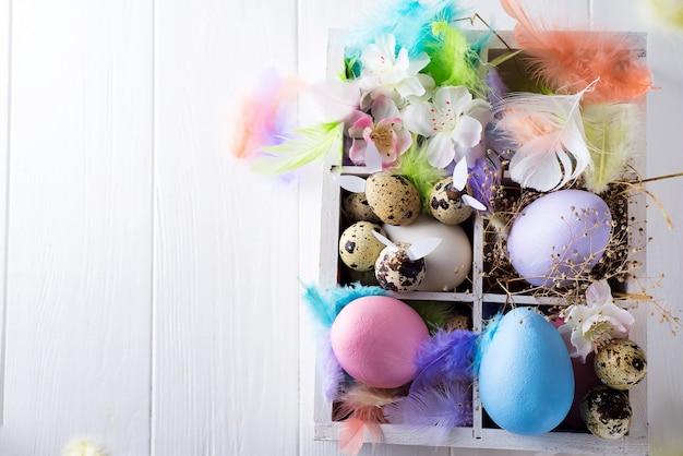 Uova di pasqua variopinte in scatola di legno su bianco