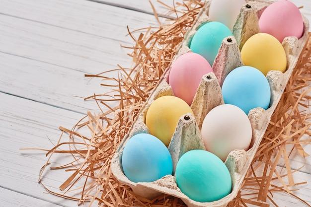 Uova di pasqua variopinte in una fine del vassoio di carta su