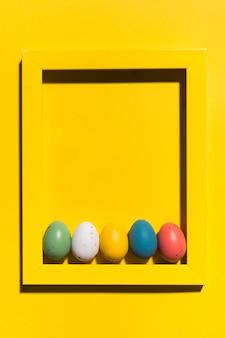 Uova di pasqua variopinte nel telaio sulla tavola gialla