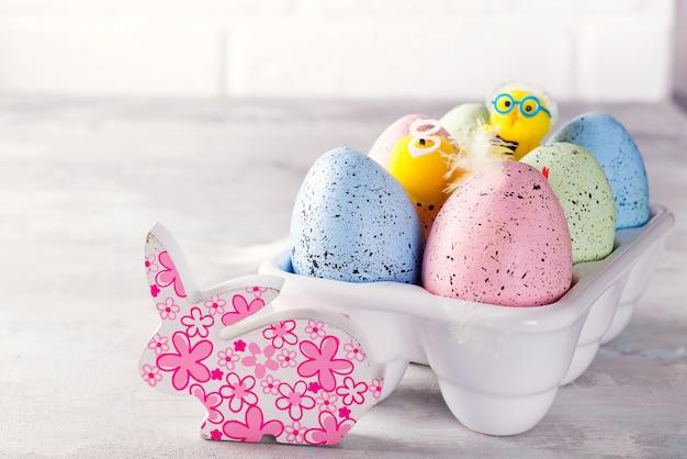 Uova di pasqua variopinte organiche con il pollo del cutie in scatola decorativa della porcellana su bianco