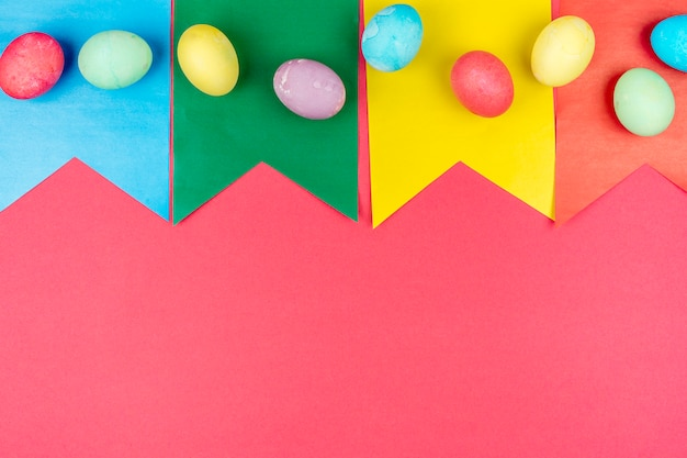 Uova di pasqua variopinte sulle bandiere di carta sulla tavola rossa