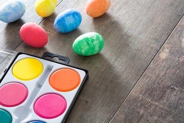 Uova di pasqua variopinte sullo spazio di legno della copia della tavola