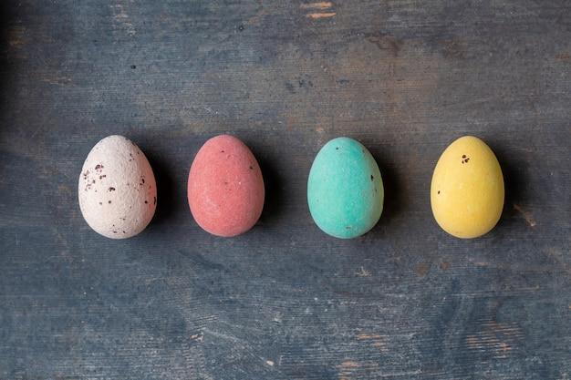 Uova di pasqua variopinte tinte in una fila su una struttura di legno d'annata del fondo, progettazione moderna dei pastelli molli