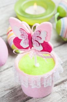 Uova di pasqua verdi variopinte e candela accesa