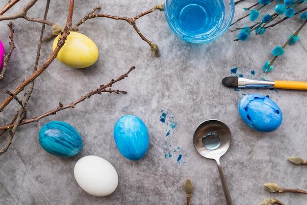 Uova di pasqua vicino a cucchiaio, ramoscelli di salice e bicchiere d'acqua
