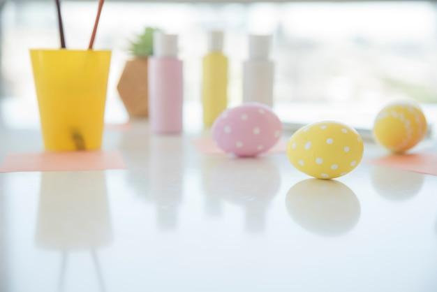 Uova di pasqua vicino a lenzuola e colori sul tavolo