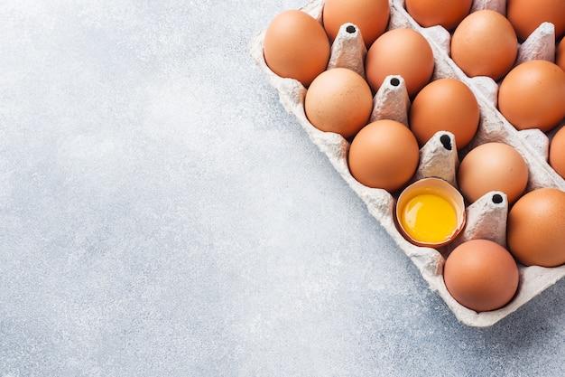 Uova di pollo crudo marrone in confezione di fabbrica su grigio