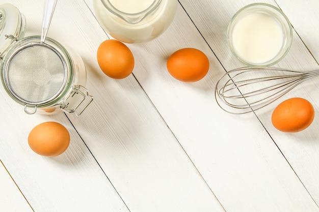 Uova di pollo marrone crudo, latte, zucchero, farina, frusta, mattarello