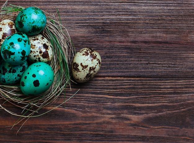 Uova di quaglia dipinte in nido naturale su fondo di legno rustico