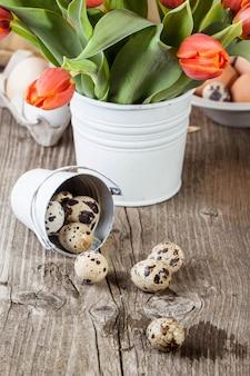 Uova di quaglia e bouquet di tulipani rossi