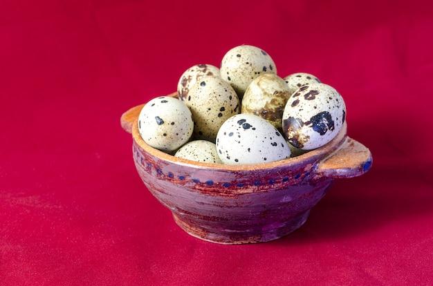 Uova di quaglia in ciotola di argilla, superficie rossa