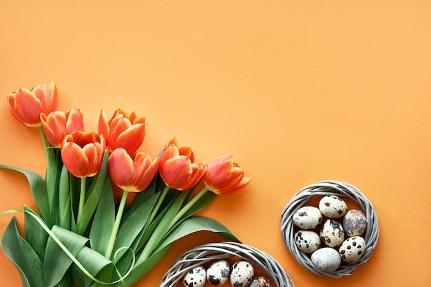 Uova di quaglia in nido di uccelli, tulipani di primavera, buste e decorazioni floreali. il piatto di pasqua giaceva su carta arancione con copia-spazio.