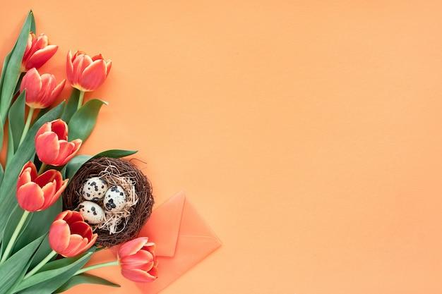 Uova di quaglia in nido di uccelli, tulipani primaverili, buste e decorazioni floreali, spazio fronte