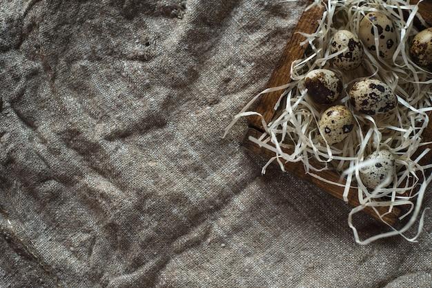 Uova di quaglia in una scatola di legno su uno sfondo di tela da imballaggio.