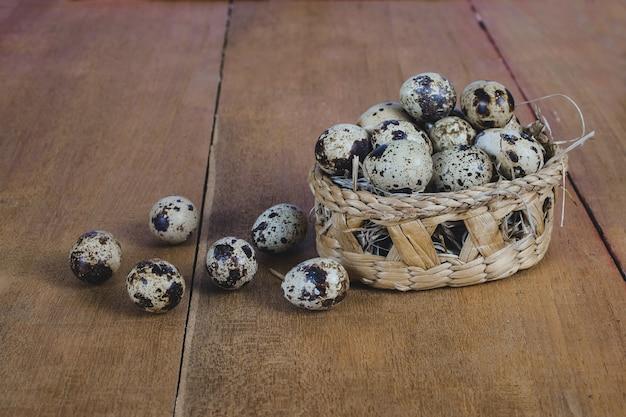 Uova di quaglia nel cesto di bambù sul vecchio tavolo di legno sfondo.