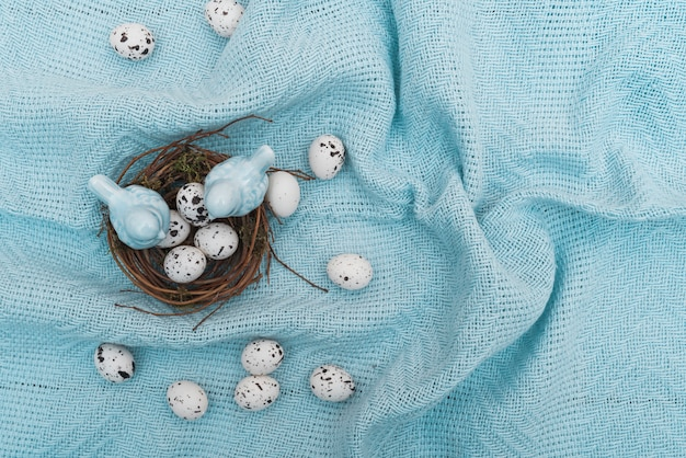 Uova di quaglia nel nido sul panno blu