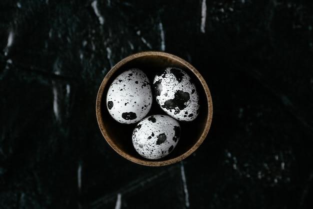 Uova di quaglia uova di quaglia crude in un contenitore. tre uova di quaglia su sfondo nero