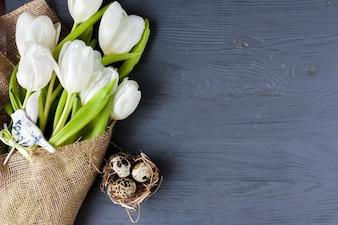 Uova di quaglia vicino a tulipani bianchi