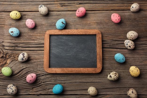 Uova di quaglie nel nido e fiori. biglietto di auguri di pasqua. vista dall'alto con spazio per i tuoi saluti