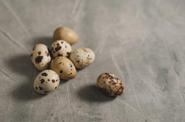 Uova di quaglie su uno sfondo grigio concreto