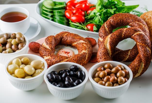 Uova di vista dell'angolo alto con la salsiccia in piatto con una tazza di tè, bagel turco, insalata su superficie bianca