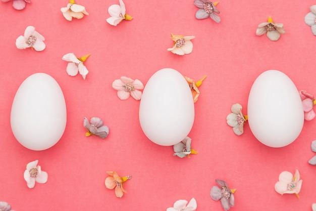Uova di vista superiore con petali di fiori sul tavolo