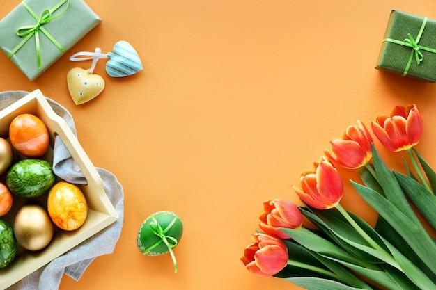 Uova dipinte, carta regalo, buste e scatole regalo. il piatto di pasqua giaceva su carta arancione con copia-spazio