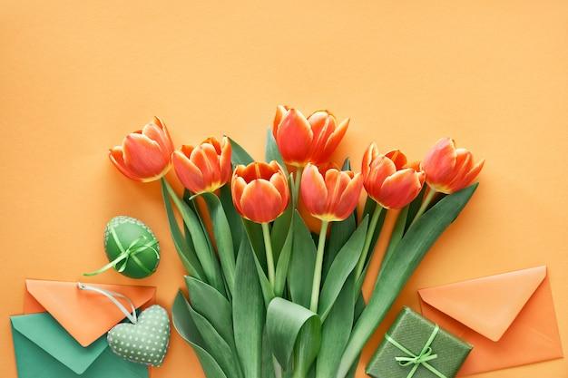 Uova dipinte, carte regalo, buste e scatole regalo. piatto di pasqua disteso su carta arancione.