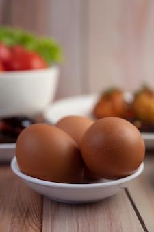 Uova disposte in una tazza su un pavimento di legno.