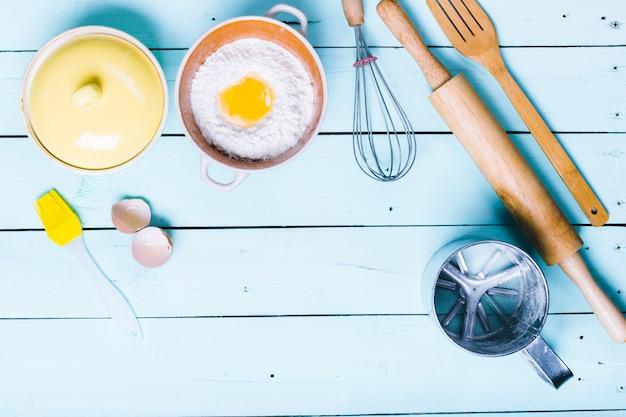 Uova e farina con un mattarello su fondo di legno